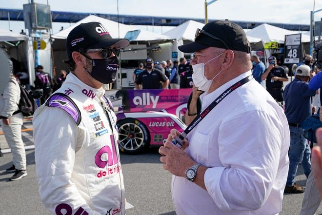 Jimmie Johnson, left, talks with team owner chip Ganassi before the start of the Rolex 24 hour auto race at Daytona International Speedway on Jan. 30, in Daytona.