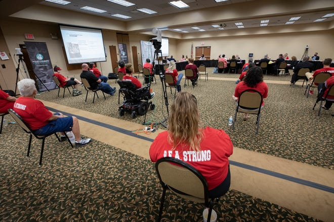 Teachers listen to the School Board debate a proposal to raise teacher pay in the district. The board decided to raise teacher pay, but not paraeducators and support staff. It also rejected a larger raise for veteran teachers sought by the teachers union.