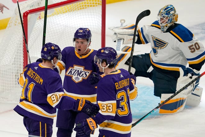 Los Angeles Kings left wing Carl Grundstrom, left, celebrates his goal with center Jaret Anderson-Dolan, second from left, and defenseman Tobias Bjornfot, second from right, as St. Louis Blues goaltender Jordan Binnington kneels in goal during the first period of an NHL hockey game Wednesday, March 17, 2021, in Los Angeles.