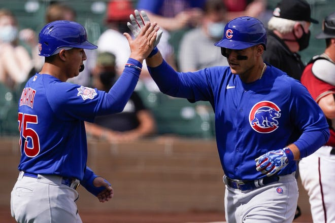 Chicago Cubs' Anthony Rizzo, right, high-fives Miguel Amaya (75) after they both score on a home run by Rizzon in the third inning of a spring training baseball game against the Arizona Diamondbacks Sunday, March 7, 2021, in Scottsdale, Ariz. [AP Photo/Ashley Landis]