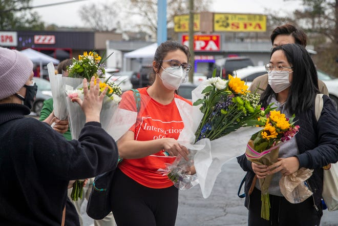 FILE - In this March 17, 2021, file photo, Roula AbiSamra, center, and Chelsey, right, prepare to lay flowers bouquets at a makeshift memorial outside of the Gold Spa in Atlanta. Asian Americans were already worn down by a year of pandemic-fueled racist attacks when a white gunman was charged with attacking three Atlanta-area massage parlors and killing eight people, most of them Asian women. (Alyssa Pointer/Atlanta Journal-Constitution via AP, File)