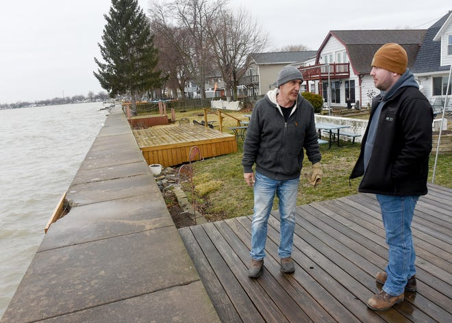 Scott Dusseau (left) of Allen Cove in Luna Pier talks with Nick Crockett as they took a look at the lake level and wind direction Thursday afternoon. The forecast called for northeast winds that may cause flooding from Lake Erie.