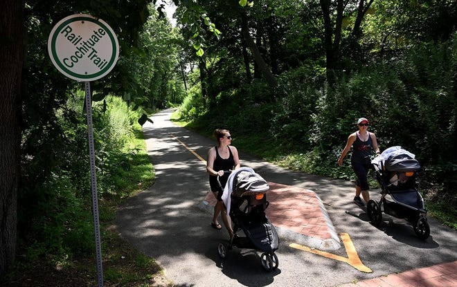A pair of walkers with strollers traverse the Cochituate Rail Trail in Framingham.