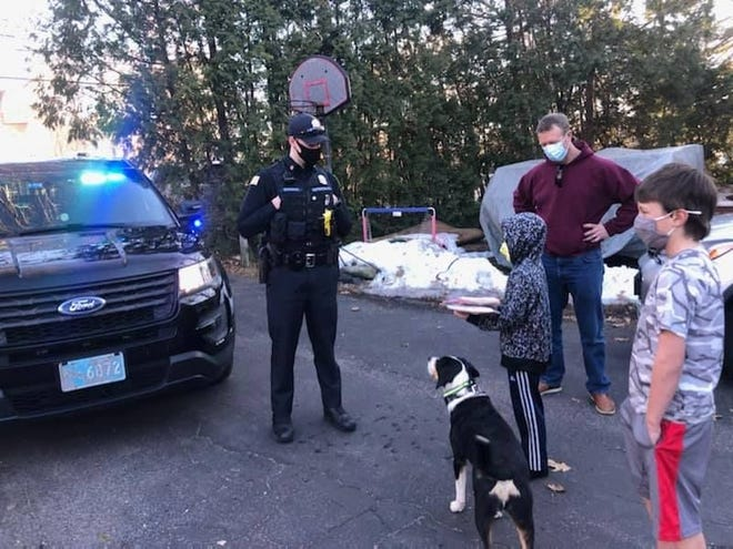 Hopkinton police officer Rob Ekross gives some gifts to Carver St. Pierre last week for his 7th birthday as Carver's father, Tom, and brother, Grady, look on.