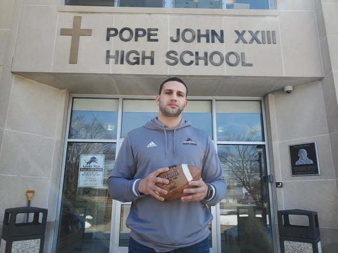 New Pope John football coach Dom Gaston stands outside the entrance to Pope John XXIII High School after being named the team's new head coach in February.
