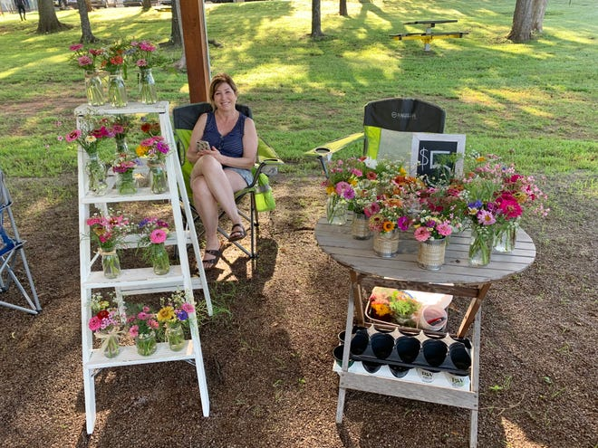 Debbie Norrid helped out last summer at the cut flower booth of her sister, Susan Snyder, at the Arcadia Farmers Market.