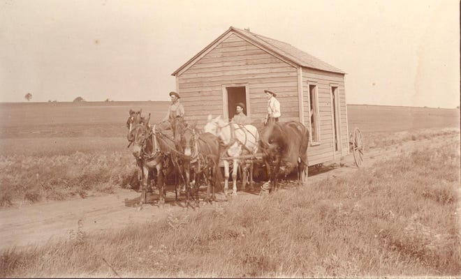 Settlers move a frame house across wide-open spaces near Perry in this pre-statehood photo. The owner paid $20 for the house.