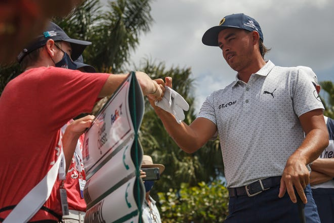Jupiter's Ricky Fowler fist-bumps a standard-bearer on the first tee of his round at The Honda Classic at PGA National Resort and Spa in Palm Beach Gardens, Fla., on Thursday, March 18, 2021.