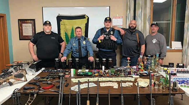 Members of the Stafford Police Department, a multi-county agency, display items--including marijuana, drug paraphernalia, U.S. currency, assets and guns --that were seized during the March 8 execution of a search warrant. on North Park Street in St. John. The suspects involved were charged and transported to Rice County Detention Center with bond set at $300,000. Pictured, left to right, are Office Petrik, Chief Gimbi, Officer Smith, Detective Wettstein and St. John Police Chief Allen Adams. Names of the persons arrested have not been released.