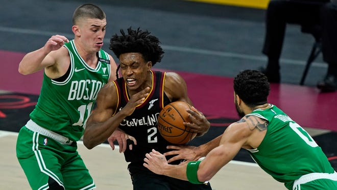 The Cavaliers' Collin Sexton drives to the basket between the Celtics' Payton Pritchard, left, and Jayson Tatum during the second half Wednesday night in Cleveland. The Cavaliers won, 117-110.