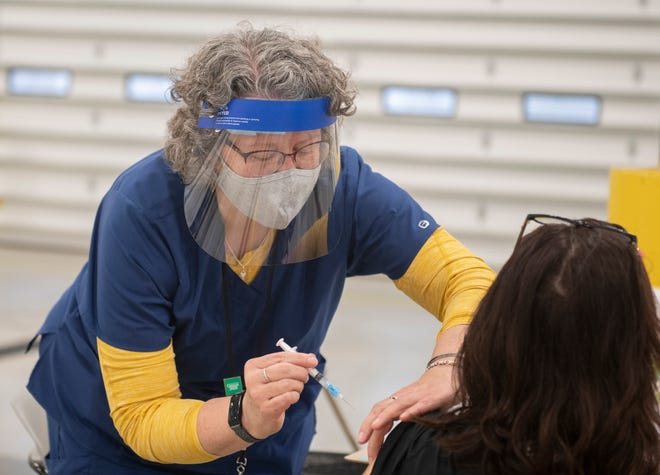 Joan Seidel, Kent City Health Commissioner, administers a vaccine during a mass vaccination clinic hosted by AxessPointe at PARTA's Summit Street facility just east of Kent State University earlier this spring.