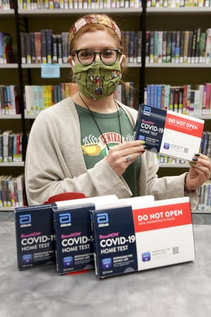 Tori Suba, a young adult specialist at the North Canton Public Library, shows off the Abbott Pharmaceutical take-home COVID tests that will soon be available at the library. The Ohio Department of Health teamed up with libraries across the state to make the free tests more accessible to Ohio residents.