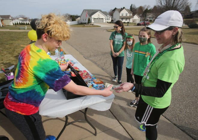 Jayden Petty takes money from Angie Ellis, a physical education teacher at T.C. Knapp Elementary, during an event selling snacks and drinks to raise money for a Perry Local family who lost everything in a fire. Jayden organized the effort with his mother, April Petty.