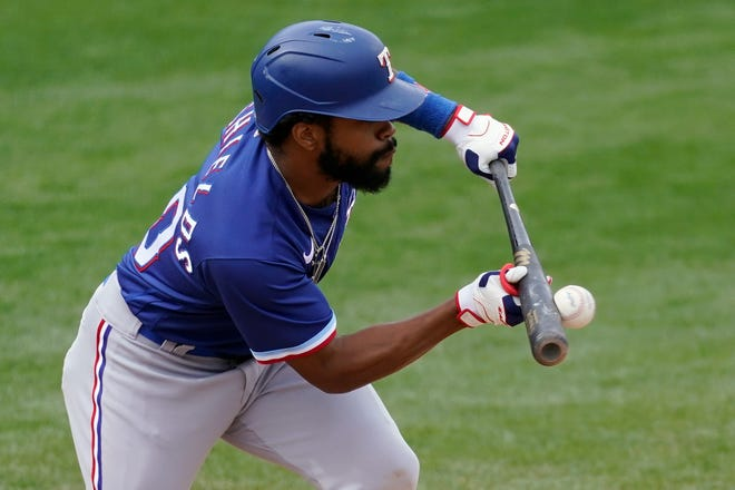 Texas Rangers' Deline DeShields bunt grounds out during the seventh inning of a spring training baseball game against the Milwaukee Brewers on Saturday in Phoenix.