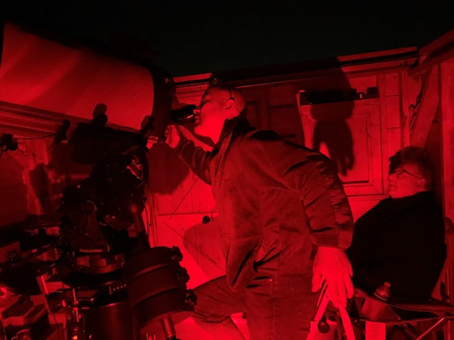 Howard Hochhalter looking through a telescope during the Messier Marathon on March 13, 2021.