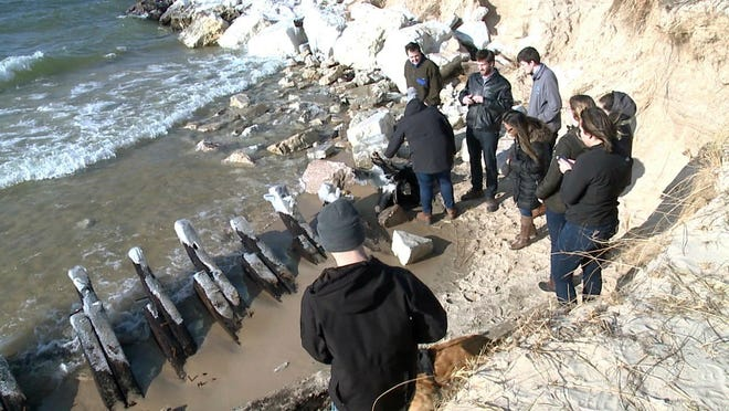 FILE - In this Dec. 10, 2018 file image made from video and provided by WXMI-TV, people look at the remains of a Lake Michigan shipwreck on a shore near Whitehall, Mich. A change in Lake Michigan water levels has revealed the shipwreck from the 1880s that is visible in western Michigan for the first time since 2018. Experts believe it's the wooden spine of the Contest, said Craig Rich, director of the Michigan Shipwreck Research Association. (WXMI-TV via AP File)