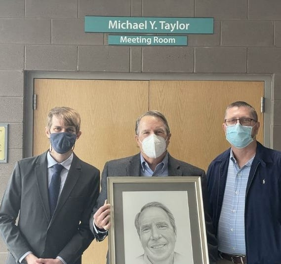 Allen Phillips-Bell, Mike Taylor, and Allen Vann stand in front of the newly named Michael Y. Taylor Meeting Room.