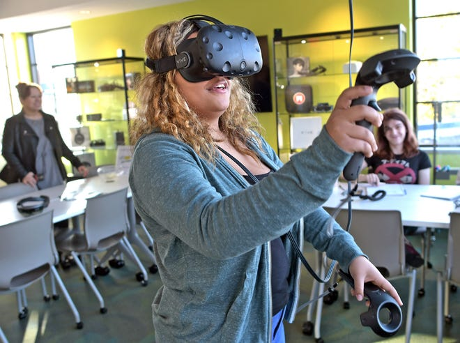 In a 2018 photo, Becker College student Mia Seter tries out a virtual reality headset during a demonstration of interactive media gaming at an open house showcasing MassDiGi technology and development.
