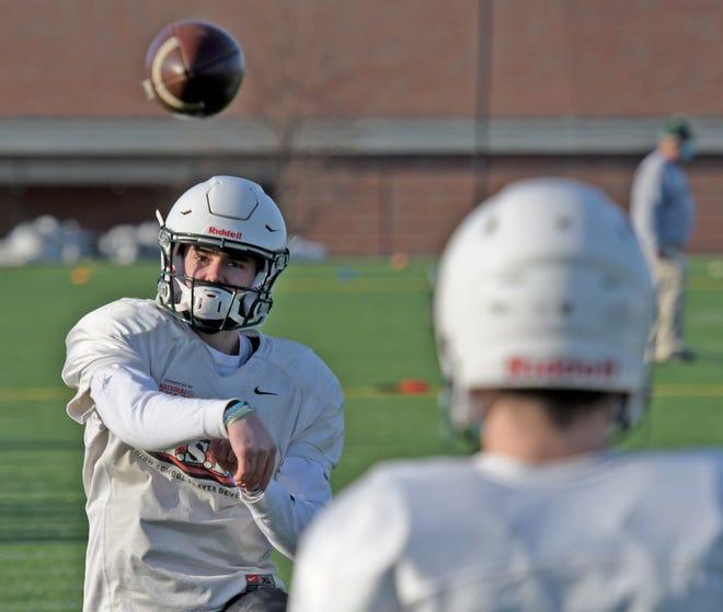 Wachusett quarterback Tucker McDonald, left, warms up at practice on Wednesday.
