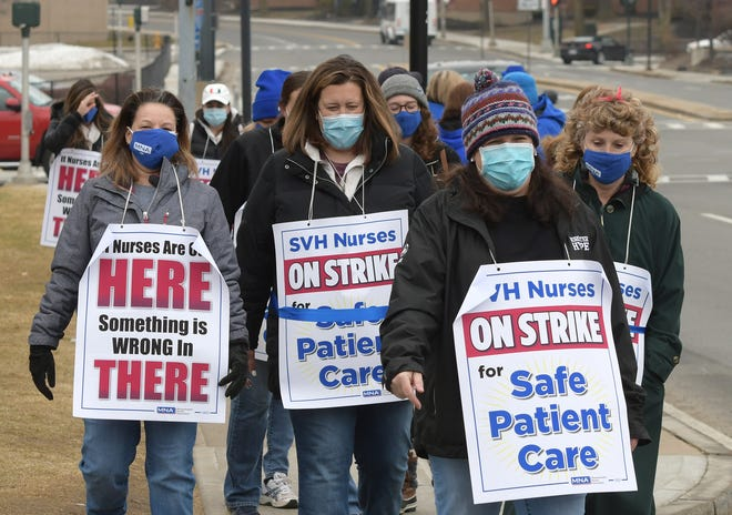 St. Vincent Hospital nurses and their supporters walk the picket line Thursday in Worcester.