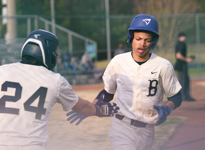 Bryant's Titus Lagunes high-fives Bryant's David Grant (2) after Grant stole home plate for Bryant's first score in Bryant's game against Pleasant Grove on March 11, 2021. [Photo/Hannah Saad]