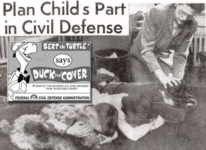 """The Fries children (Eddie, Bobby and Susan) of Grandview Heights and their dog, Lixie, are shown under the watchful eye of their mother, practicing the """"Duck and Cover"""" technique for protecting themselves from flying debris that might result from the detonation of a nuclear weapon nearby."""