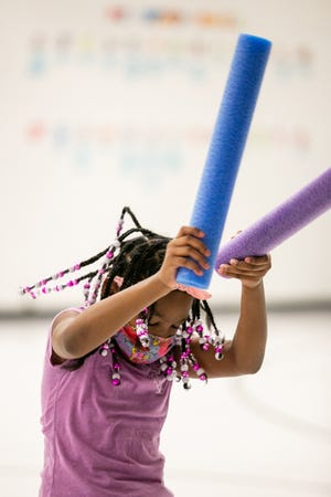 Pointview Elementary School third-grader Ja'Queen Edwards dances with her drumming noodles during a freestyle moment in a fitness-drumming class held by physical-education teacher Alisa Franklin and music teacher Alex Chapman at the school March 16.