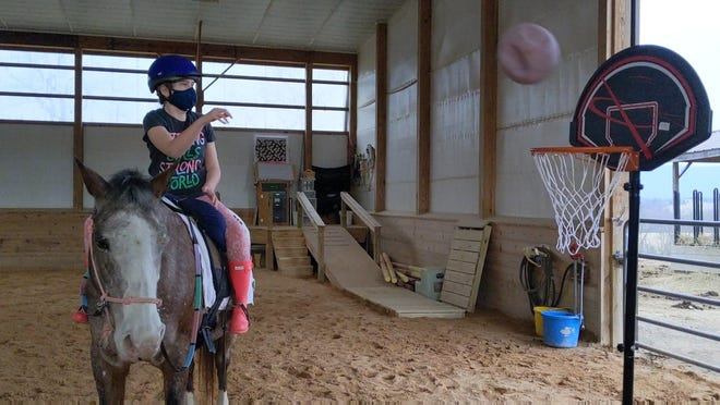 Grace is on her horse Rose, practicing her shooting before taking part in the hoop-a-thon later this month