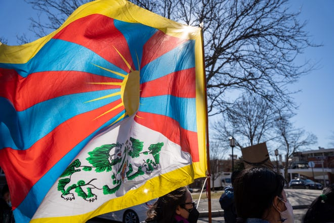 A protester holds the Tibetan flag on March 13 outside Tuft's Confucius Institute.