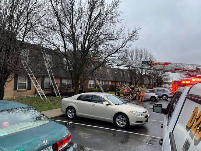 Firefighters from Colerain Township Department of Fire and Emergency Medical Services use a ladder truck at a Wednesday apartment fire that caused six families to be displaced from their residences.