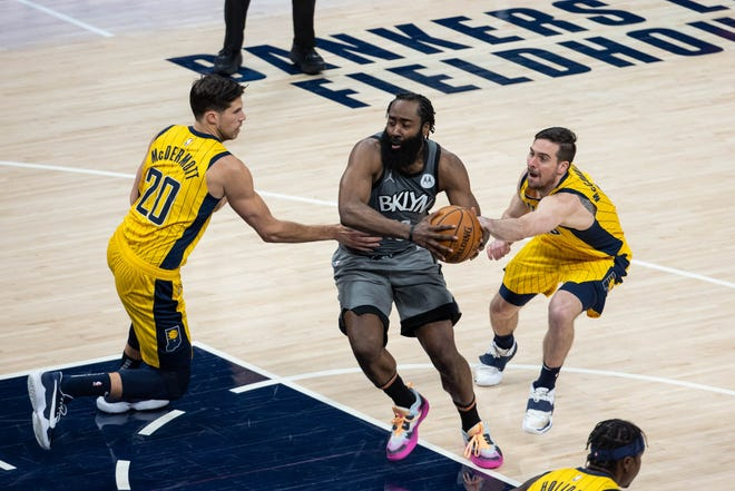 Mar 17, 2021; Indianapolis, Indiana, USA; Brooklyn Nets guard James Harden (13) cuts toward the basket while Indiana Pacers forward Doug McDermott (20) and guard T.J. McConnell (9) defend in the third quarter at Bankers Life Fieldhouse. Mandatory Credit: Trevor Ruszkowski-USA TODAY Sports