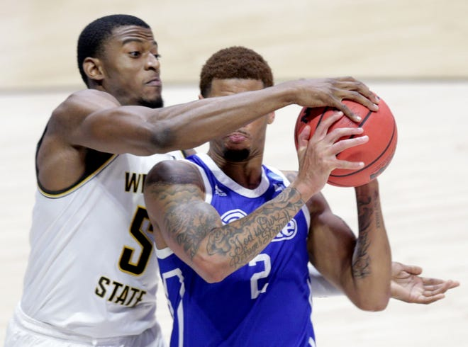 Wichita State Shockers forward Trey Wade (5) reaches around Drake Bulldogs forward Tremell Murphy (2) for the ball during the first round of the 2021 NCAA Tournament on Thursday, March 18, 2021, at Mackey Arena in West Lafayette, Ind.
