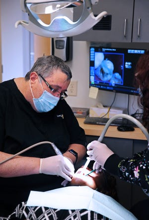 Paul Levine, DDS, of Levine Dental in Brown Deer, puts in a crown for patient Gloria Pitchford-Nicholas on Thursday, March 18, 2021, who was being treated for a fractured cusp. Assisting Levine is Lisa Karau on the right.