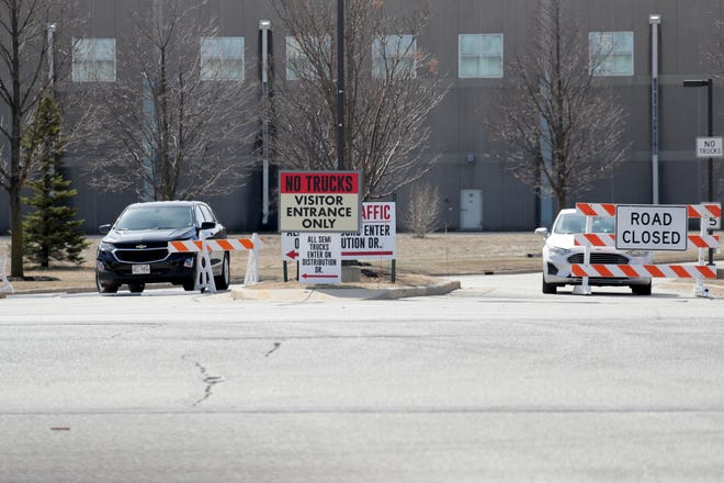 Vehicles are parked at an entrance to the Roundy's warehouse in Oconomowoc on Thursday. Two employees were killed at the warehouse Tuesday night and the suspect is also dead after a crash in Milwaukee on Wednesday morning.