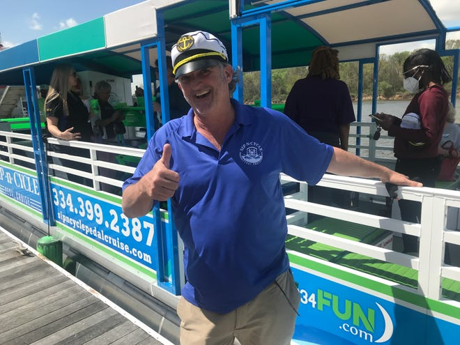"""Sip-N-Cycle owner Stuart """"Capt. Stu"""" Lackey helps passengers board his pontoon boat Thursday in downtown Montgomery."""