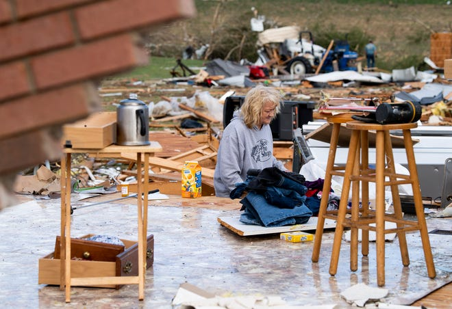 Sherrell Eaton salvages items from her home near the Enterprise community in Chilton County, Ala., on March 18, 2021, after storms hit the area.
