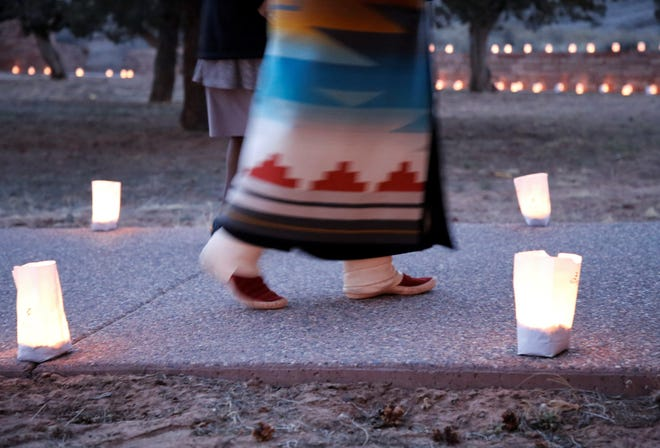 Miss Navajo Nation Shaandiin Parrish walks by luminarias as part of tribute to tribal members who died of COVID-19 in an event on March 17 in Window Rock, Arizona.