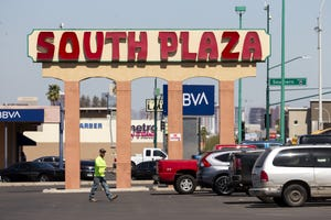A man walks past the sign at South Plaza in Phoenix on March 18, 2021.