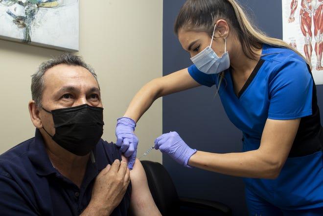 Medical assistant Reeni Ramirez (right) administers the Moderna COVID-19 vaccine to Baldemot Peralta (left) at Clinica La Familia in Mesa on March 18, 2021.