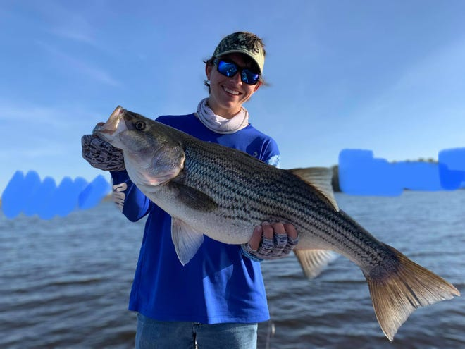 Alex Williams holds up a monster striped bass he caught on Lake Talquin on a recent trip with his dad, Colt.