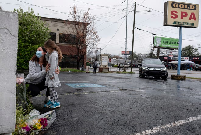 Mallory Rahman and her daughter Zara Rahman, 4, pay their respects  to victims outside Gold Spa massage parlor in Atlanta following the shootings.