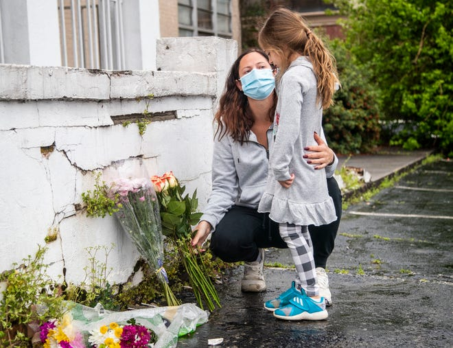 Mallory Rahman and her daughter Zara place flowers near a makeshift memorial outside of the Gold Spa in Atlanta,  March 17, 2021.
