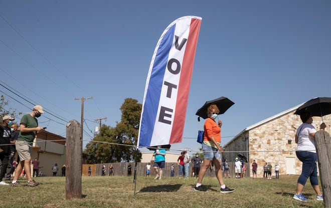 People wait in line at an early voting location at the Pflugerville ISD Rock Gym in Pflugerville on Tuesday October 13, 2020.