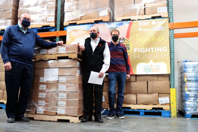 Donnie Seale, the meat and seafood supervisor for the Amarillo region of United Supermarkets, and Dennis Irlbeck, market manager for Market Street, along with Zack Wilson, the executive director of the High Plains Food Bank,  stand beside approximately 396 hams donated to the High Plains Food Bank earlier this week.