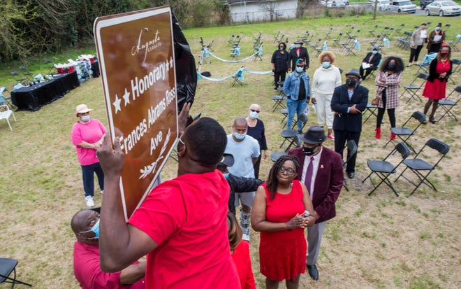 A man unveils the new honorary street sign in honor of Frances Abrams Ross during the Honorary Street Sign Unveiling and Memorial Garden Dedication Ceremony at the Marion Homes neighborhood in Augusta, Ga. Friday morning March 19, 2021.
