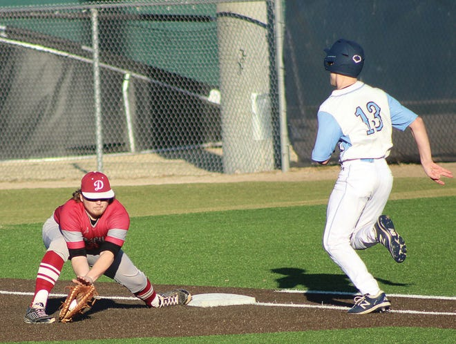 Dewey High School first baseman Michal Caswell, left, makes the low catch in time to make an out during baseball action this month against the Bartlesville Bruin jayvee.