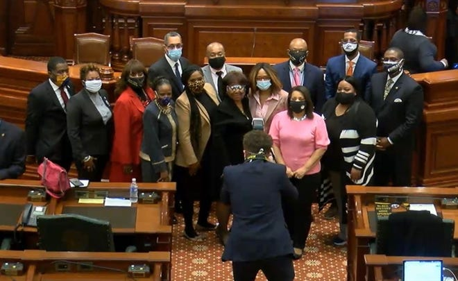 Members of the Illinois Legislative Black Caucus pose for a photo on the House floor after passing a health care reform bill that was part of the Caucus' four-pillar legislative agenda.