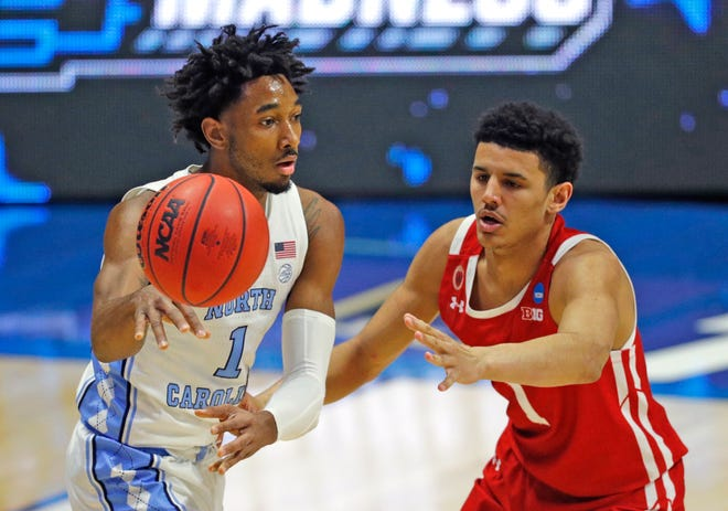 North Carolina Tar Heels guard Leaky Black (1) passes the ball guarded by Wisconsin Badgers guard Jonathan Davis (1) during the first round of the 2021 NCAA Tournament on Friday, March 19, 2021, at Mackey Arena in West Lafayette, Ind.