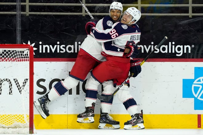 Jack Roslovic (96) hugs Seth Jones (3) after Jones' winning goal against the Carolina Hurricanes with 51 seconds left in overtime Thursday at PNC Arena in Raleigh, N.C. It was Jones' second goal of the game and third of the season.