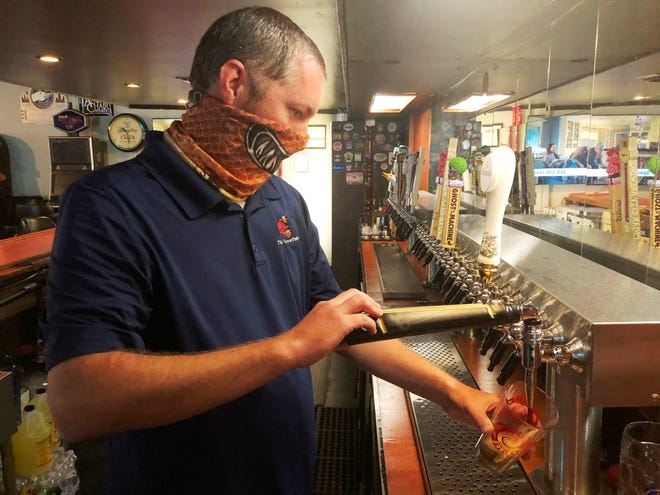Steven Robison, owner of the Thirsty Crawfish in Houma, draws a beer Friday.